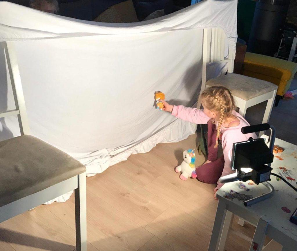 Schattenspiele mit Lampe und Bettlaken bei einer Quarantäne mit Kind
