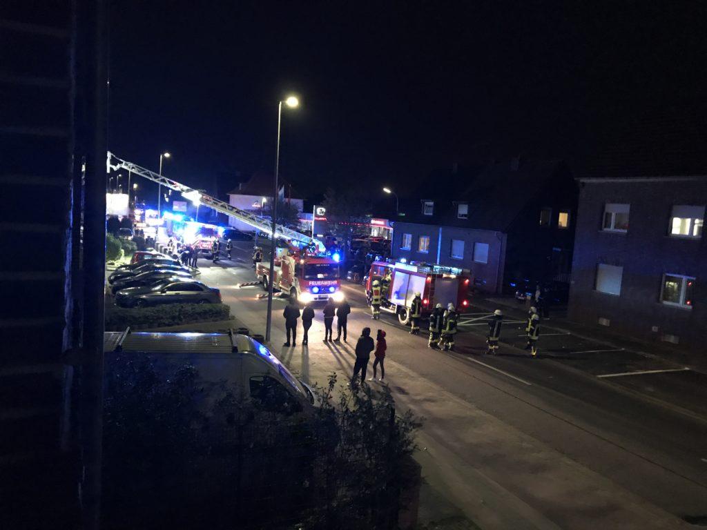 Anwohner warten auf der Straße bei einem Feuerwehreinsatz in einem Mehrfamilienhaus.